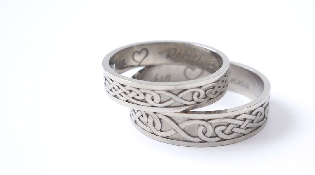 White gold wedding rings with a celtic knotwork on the outside.