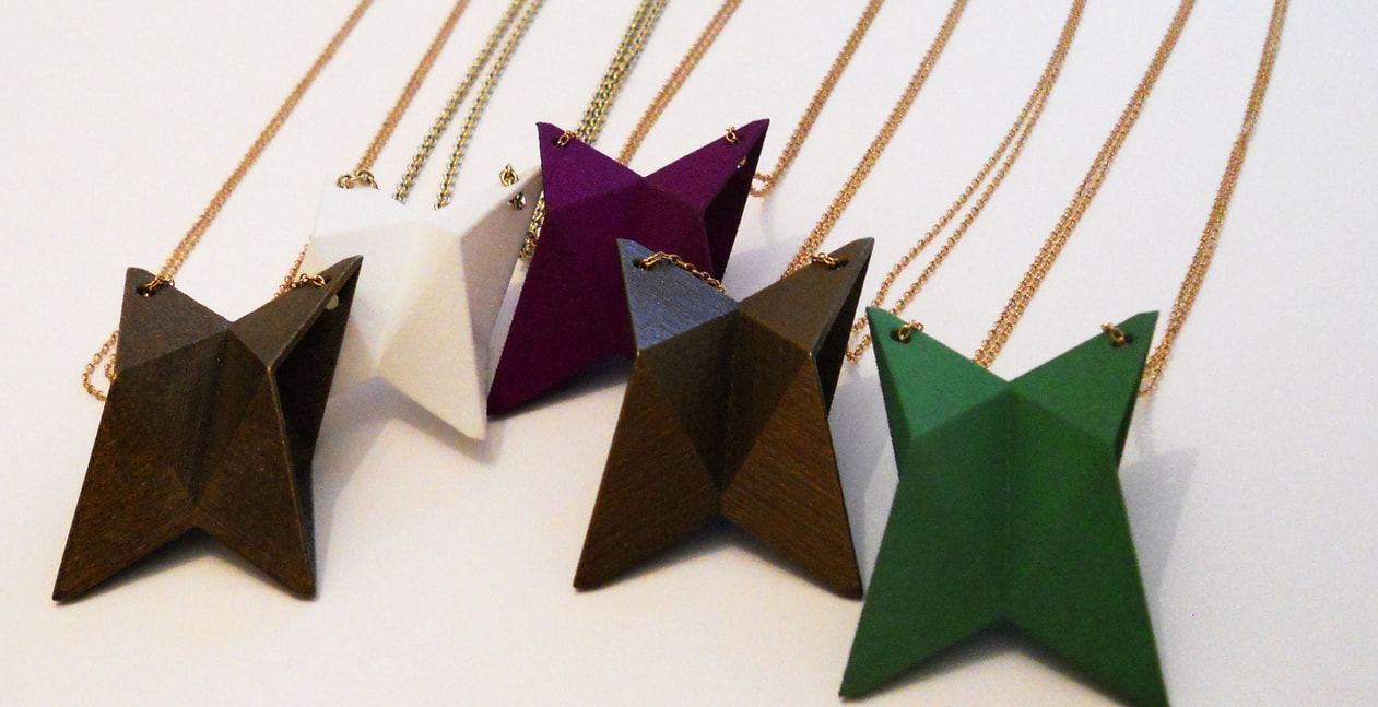 3D printed, folded ships. Printed in plastic and steel. The jewellery can be worn as a necklace.