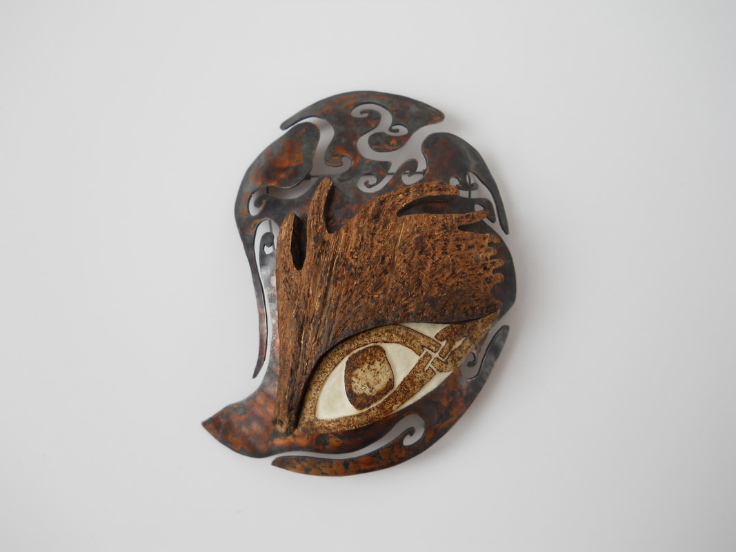 Identity brooch made of copper, coconut shell and bone with an eye burned into the bone.